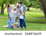 family with dog in the park on... | Shutterstock . vector #568876639