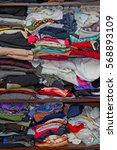 Small photo of clothes in piles stacked in disarray