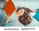 girl reads a book lying at... | Shutterstock . vector #569057575