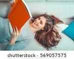 girl reads a book lying at... | Shutterstock . vector #569057575