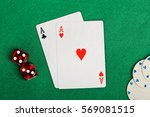 Small photo of two aces, red dice and poker chips on green felt