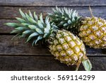 pineapple placed on a wooden... | Shutterstock . vector #569114299