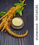 Small photo of Groats amaranth in a clay bowl, brown flower with green leaves on a background of wooden boards