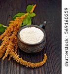 Small photo of Flour amaranth in a clay cup, brown flower with green leaves on a background of dark wood planks