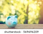 blue piggy bank on wooden table ... | Shutterstock . vector #569696209