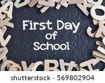 """Small photo of """"First Day of School"""" written on copyspace with pile of wooden alphabet"""