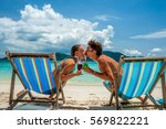 couple in loungers clinking... | Shutterstock . vector #569822221