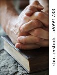 Hands Folded In Prayer Over A...