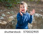 Small photo of Happy little Caucasian boy with sitting on rocks and clapping hands of joy. Happy little child stock image. Weekend coming, happy family event