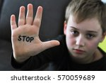 Small photo of Small abused boy holding his hand with the word 'STOP' written on it. Concept of domestic violence and child abusement.