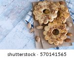 Small photo of Almonds and ring cookies, strewed with chopped nuts, on paper and on a checkered napkin on an old wooden table.