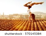 woman performs a handstand on a ... | Shutterstock . vector #570145384