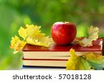 Apple and leaves on book. - stock photo
