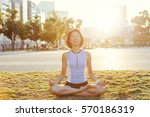 woman doing yoga at sunset on... | Shutterstock . vector #570186319