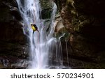 Man Rappelling Down A Waterfal...