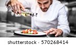 handsome chef pouring olive oil ... | Shutterstock . vector #570268414