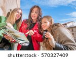 3 girls on holiday  reading map.... | Shutterstock . vector #570327409