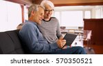 senior couple sitting on couch... | Shutterstock . vector #570350521