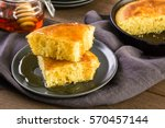 Stock photo slice of sweet cornbread with honey on the plate 570457144
