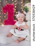 Small photo of Cute girl celebrating her first birth day in cozy airy fairy white dress with big red flower number one close to fancy couch.