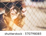 boy with hands on a fence  kid... | Shutterstock . vector #570798085