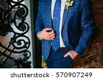 man in a blue suit holds a tie  ... | Shutterstock . vector #570907249