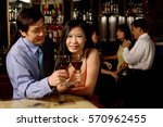 couple holding wine glasses ... | Shutterstock . vector #570962455