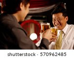 two men drinking beer together | Shutterstock . vector #570962485