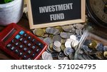 Small photo of Word INVESTMENT FUND on mini chalkboard and coin in the jar with red calculator,green plant and clock on wooden base. Financial Concept.