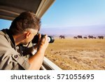 man taking photo of elephants... | Shutterstock . vector #571055695