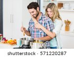 smiling young couple cooking... | Shutterstock . vector #571220287