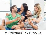 smiling friends sitting on sofa ... | Shutterstock . vector #571222735