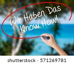 Small photo of Woman Hand Writing Wir Haben Das Know How! (We Have the Know-How in German) with black marker on visual screen. Isolated on nature. Business concept. Stock Photo