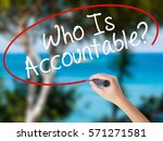 Small photo of Woman Hand Writing Who Is Accountable? with black marker on visual screen. Isolated on nature. Business concept. Stock Photo
