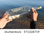 Small photo of man hands holding a bottle with message inside - message in a bottle