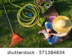 Woman having a coffee break while working in the garden, gardening tools around. - stock photo