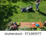 Woman wearing wellington boots mowing grass with lawn mower in the garden, gardening tools concept  - stock photo