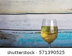 glass of white wine being... | Shutterstock . vector #571390525