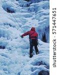 Man Climbing On Frozen Waterfall