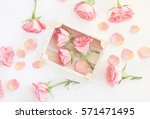 Stock photo little light pink roses in wooden box and petals scattered over wooden table soft white haze toned 571471495