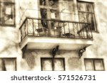 Small photo of Plastered building facade in evening light with many windows and a beautifully adorned smithery balcony, textured in sepia tones from the front side in old fashion style.