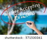 Small photo of Woman Hand Writing We Are Accepting Bitcoins with black marker on visual screen. Isolated on nature. Business concept. Stock Photo