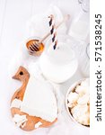 Small photo of Fresh dairy products milk, cottage cheese Adygei cheese , wheat, white wood background