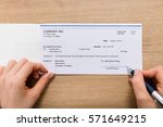 Small photo of Close-up Of A Person Hand Signing Paycheck At Wooden Desk