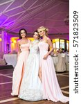 Small photo of Bride and girls in pink dress pose in the middle of dancehall