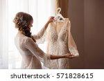 bride in peignoir looks to... | Shutterstock . vector #571828615