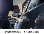 Auto thief in black balaclava trying to break into car with screwdriver. Car thief, car theft - stock photo