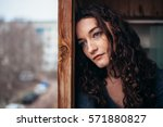 Stock photo beautiful sad lonely girl sitting near the window is missing 571880827