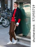 Small photo of MILAN - JANUARY 14: Man with brown Adidas trousers and red sweater before Emporio Armani fashion show, Milan Fashion Week street style on January 14, 2017 in Milan.