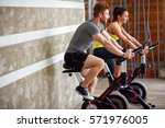 couple exercises legs on bike... | Shutterstock . vector #571976005